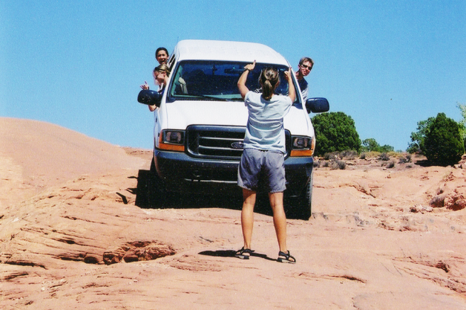Image of people and truck on desert rocks.