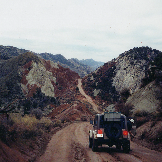 Image of jeep on road into mountains.