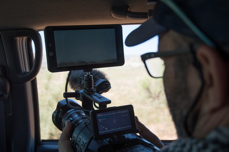 Image of camera filming out car window.