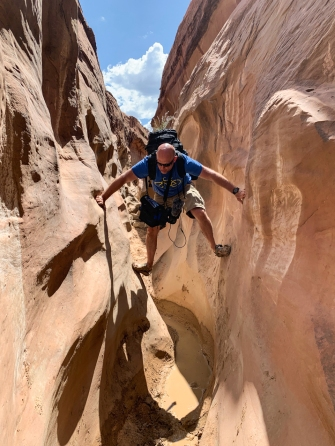 Image of man climbing through canyon